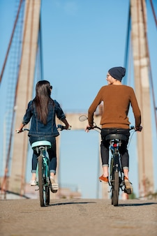 Gemeinsam ihre fahrt genießen. rückansicht eines schönen jungen paares, das fahrrad entlang der brücke fährt und sich ansieht