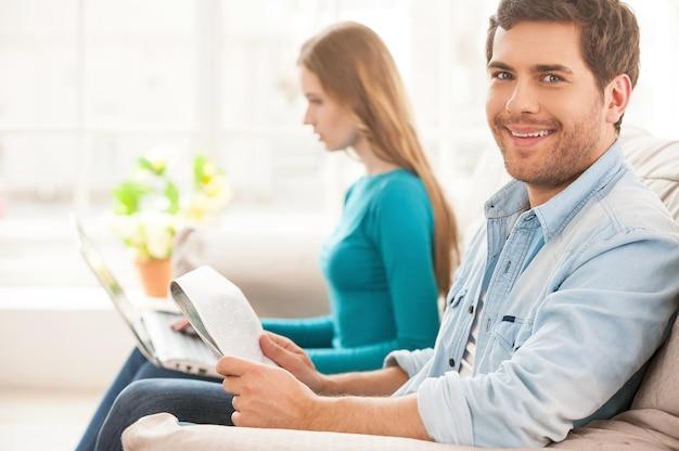 Gemeinsam ihren freien tag genießen. schöner junger mann, der auf der couch sitzt und eine zeitung hält, während seine frau im hintergrund sitzt und am laptop arbeitet