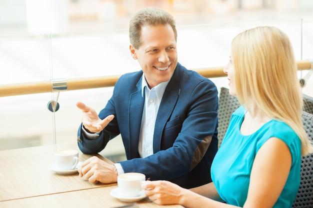 Gemeinsam im café entspannen. schönes reifes paar, das kaffee trinkt und miteinander spricht, während es im café sitzt?