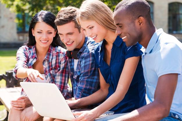 Gemeinsam im netz surfen. vier glückliche junge leute, die laptop betrachten und lächeln, während sie zusammen im freien sitzen