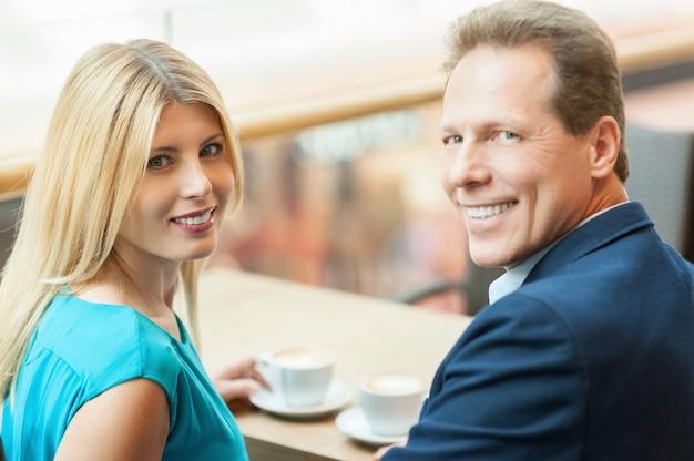 Gemeinsam kaffee trinken. schönes reifes paar, das zusammen kaffee trinkt und beim sitzen im café in die kamera schaut?