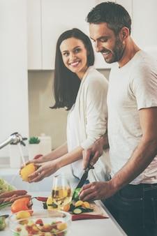 Gemeinsam kochen macht spaß. schönes junges liebespaar, das zusammen in der küche kocht