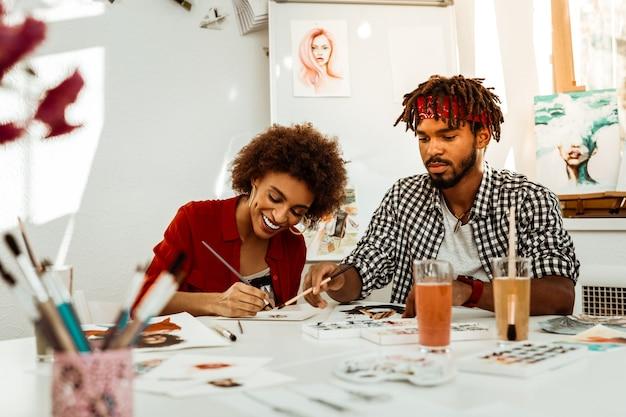 Gemeinsam malen. paar inspirierte kunststudenten, die sich beim malen mit aquarell zusammen wohl fühlen