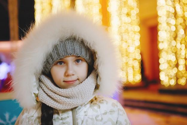 Gemeinsam spaß bei einer weihnachtsfee haben. junges fröhliches paar geht mit heißen getränken spazieren, genießt, warm angezogen, sieht sich an und lacht