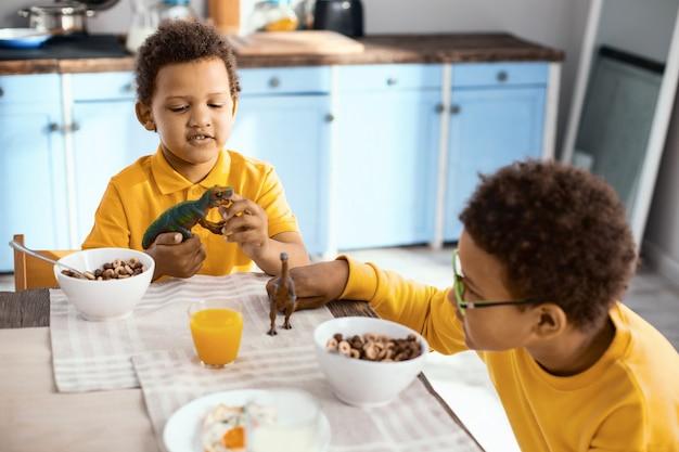Gemeinsam spaß haben. charmante kleine jungen, die mit ihren spielzeugdinosauriern spielen, während sie am tisch sitzen und müsli essen