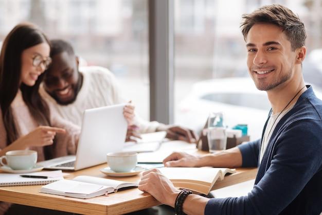 Gemeinsam studieren. junger hübscher kerl, der lächelt, während er im café auf hintergrund seiner studierenden mitschüler sitzt.