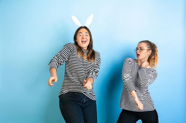 Gemeinsam tanzen. junge emotionale frauen lokalisiert auf blauem studiohintergrund der steigung. konzept der menschlichen emotionen, gesichtsausdruck, freundschaft, anzeige. schöne kaukasische weibliche modelle in freizeitkleidung.
