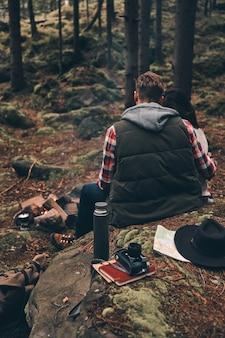 Gemeinsam wohlfühlen. rückansicht eines jungen paares, das sich am lagerfeuer aufwärmt, während es im wald sitzt