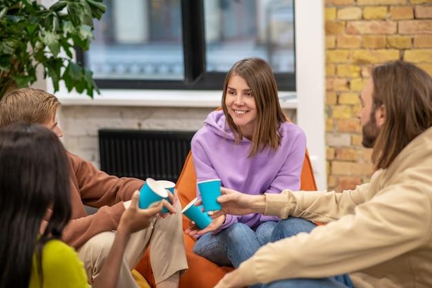 Gemeinsame interessen. fröhlich junge menschen kommunizieren interessanterweise freundlich und halten ihre freizeit im büroerholungsgebiet Premium Fotos