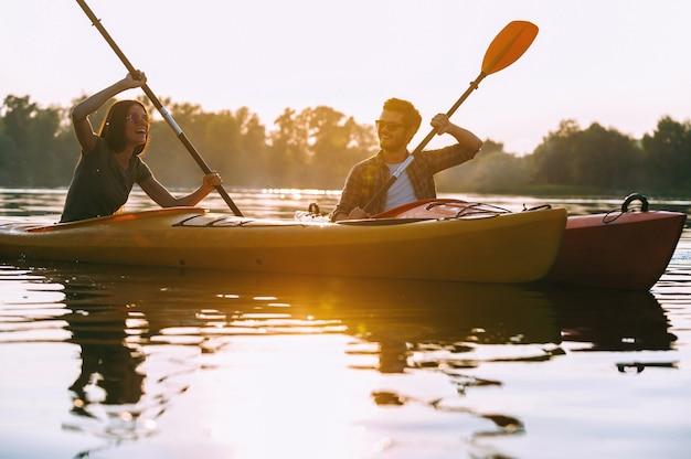 Gemeinsames kajakfahren macht spaß. schönes junges paar, das zusammen auf dem see kajak fährt und lächelt