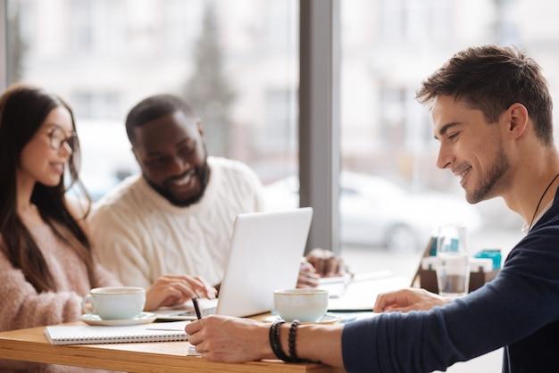 Gemeinsames projekt. seitenansicht des jungen lächelnden mannes, der notizen macht, während er zusammen mit seinen kommilitonen an der cafeteria studiert.