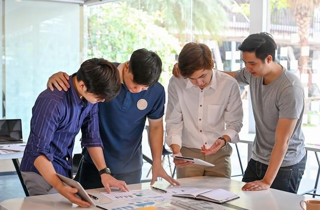 Gemeinsames startprojekt mit einer gruppe junger männer, die brainstorming auf papier und tablet betreiben.