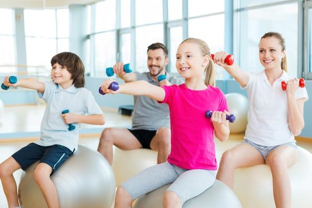Gemeinsames training macht spaß. glückliche sportliche familie, die zusammen im sportverein trainiert