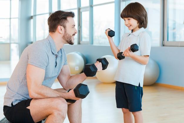 Gemeinsames training macht spaß. glücklicher vater und sohn, die mit hanteln trainieren und lächeln, während sie beide im fitnessclub stehen