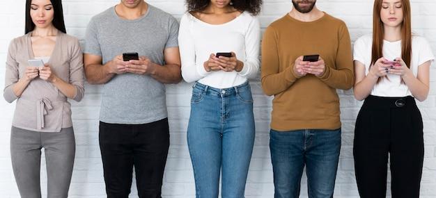 Gemeinschaft junger leute, die auf handys sms schreiben
