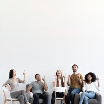 Gemeinschaft junger leute mit nach oben zeigenden fingern