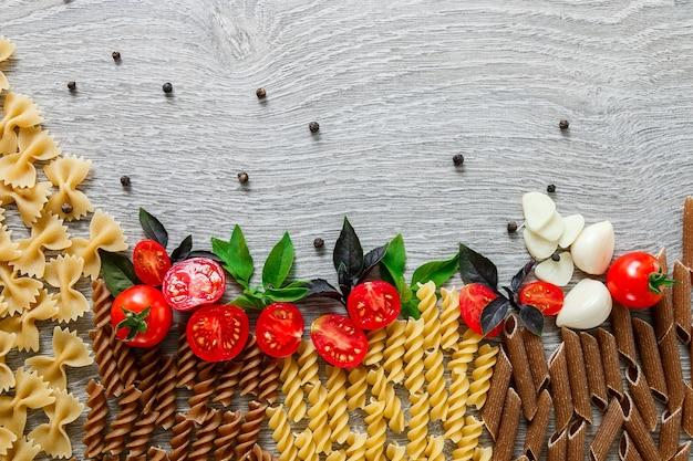 Gemischt von zwei farbigen nudeln in der nähe von tomaten, knoblauch und basilikum auf grauem holzhintergrund. roher nudelrahmen. speicherplatz kopieren. flach liegen.