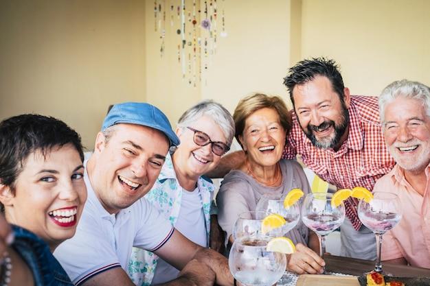 Gemischte altersgruppe von kaukasiern, die zusammen spaß haben und eine veranstaltung feiern, die einen cocktail mit rotwein aus weißem wodka trinkt
