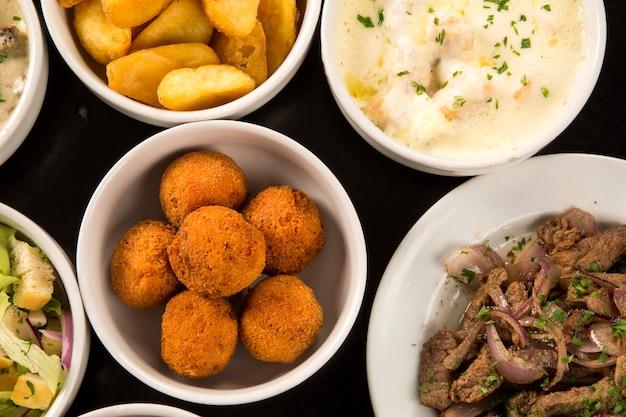 Gemischte brasilianische snacks, darunter gebäck, brathähnchen, salate, suppen, pommes und kibe