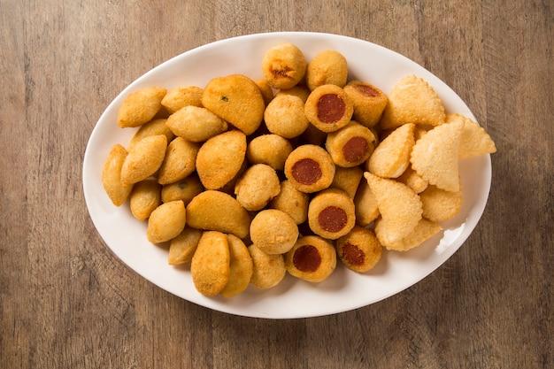 Gemischte brasilianische snacks gebraten auf hölzernem hintergrund.