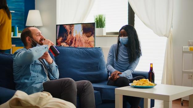 Gemischte freunde mit schutzmaske, die während der neuen normalen party sprechen, abstand halten, auf dem sofa sitzen, bier trinken und schlangen essen. gruppe von multiethnischen menschen, die geselligkeit und freizeit genießen