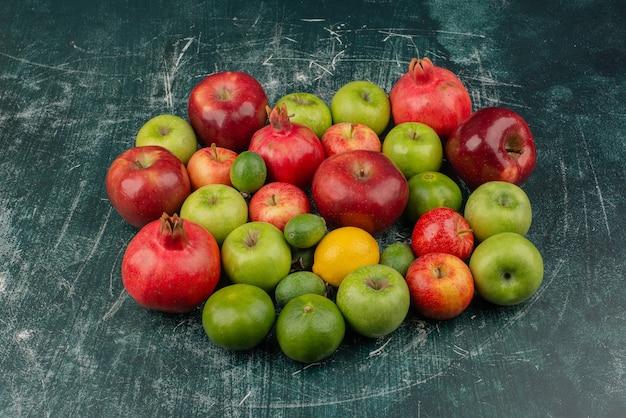 Gemischte frische früchte auf marmoroberfläche verstreut