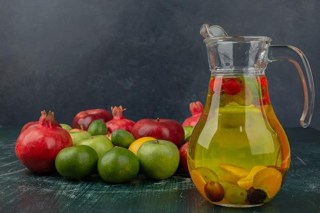 Gemischte frische früchte und ein glas saft auf marmortisch.