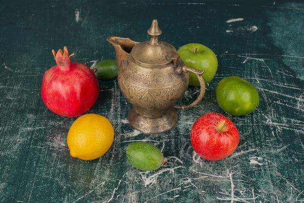 Gemischte frische früchte und klassische teekanne auf marmortisch.