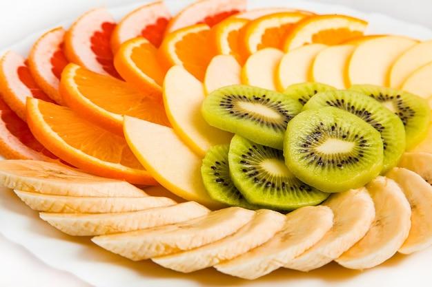 Gemischte früchte in weißer platte isoliert auf weiß