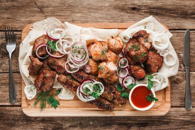 Gemischte gegrillte fleischplatte. verschiedenes köstliches gegrilltes fleisch serviert auf pittabrot mit kräutern, zwiebeln und tomatensauce, ansicht von oben.
