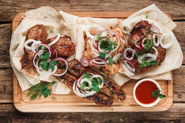 Gemischte gegrillte fleischplatte. verschiedenes köstliches grillfleisch serviert mit kräutern, zwiebeln und tomatensauce.