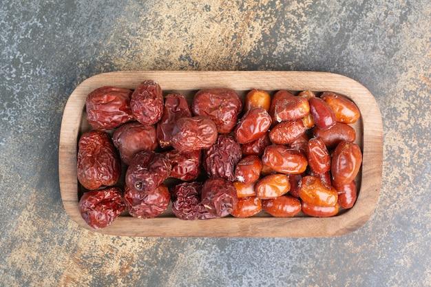 Gemischte gesunde trockenfrüchte auf holzteller. hochwertiges foto