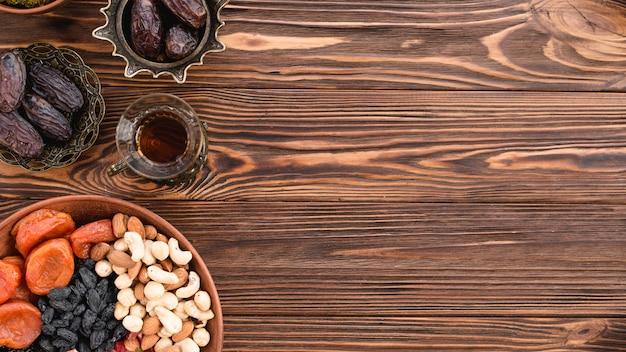 Gemischte getrocknete früchte; nüsse; termine und tee auf dem ramadan-festival über dem schreibtisch aus holz