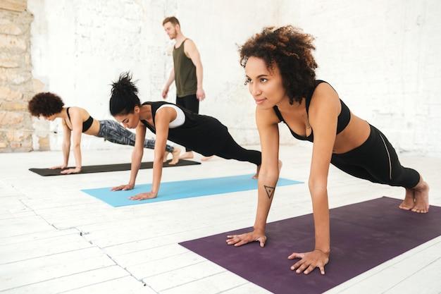 Gemischte gruppe junger leute, die yoga-klasse machen