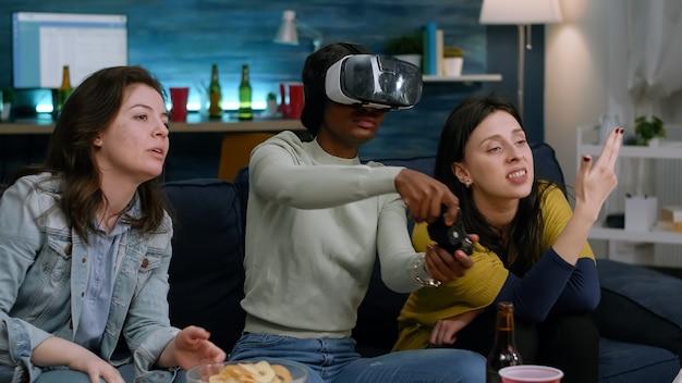 Gemischte gruppe von freunden, die afroamerikanische frau mit virtual-reality-headset führen, die simulationsspiel mit controller spielt. afro-kaukasische frau verliert online-videospiel-wettbewerb