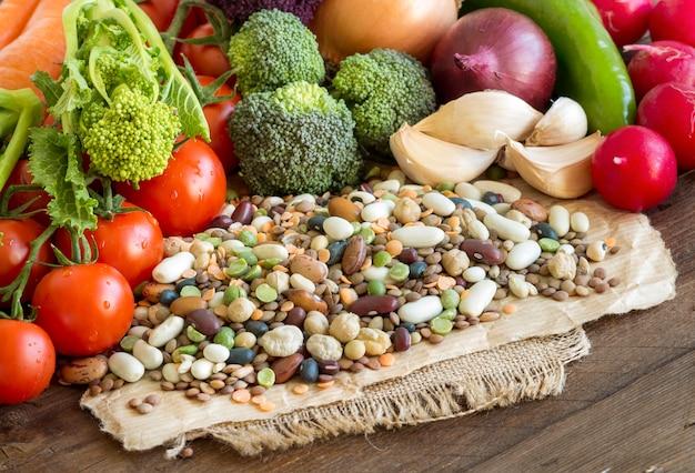 Gemischte hülsenfrüchte und rohes gemüse auf einem braunen holztisch schließen oben