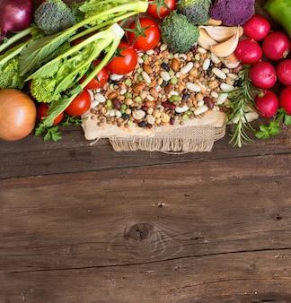 Gemischte hülsenfrüchte und rohes gemüse auf einer braunen hölzernen tischoberansicht mit kopienraum