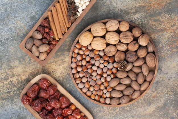 Gemischte nüsse mit zimtstangen und getrockneten früchten auf holzteller. hochwertiges foto