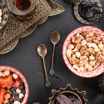 Gemischte nüsse; tee; trockenfrüchte und metallische löffel auf schwarzem konkretem hintergrund