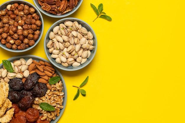 Gemischte nüsse und getrocknete früchte auf einem teller auf gelbem hintergrund mit kopienraum. symbole des jüdischen feiertags von tu bishvat gesunder snack - mischung aus bio-nüssen und trockenfrüchten.