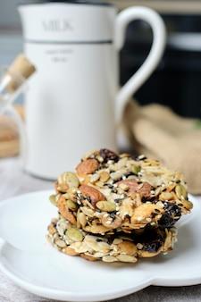 Gemischte nüsse und getrocknete früchte und samen florentiner, glutenfreie vollwertkost gesunde kekskekse. auf cafe tisch gesetzt.