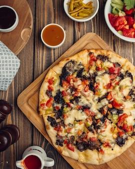Gemischte pizza mit fleisch, tomaten, paprika