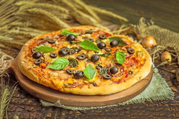 Gemischte pizza mit hühnchen, pfeffer, oliven, zwiebeln, basilikum auf pizza-board