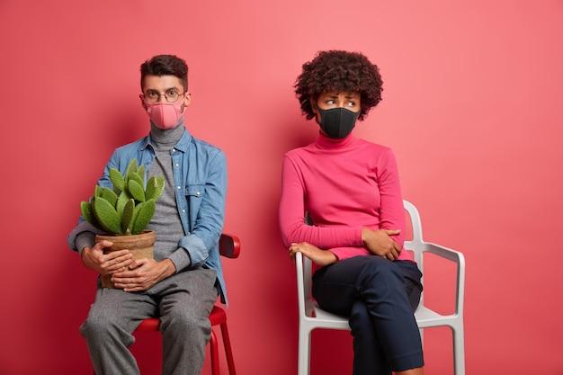 Gemischte rasse junge frau und mann tragen schutzmasken haben schlechte laune nebeneinander sitzen hält kaktus