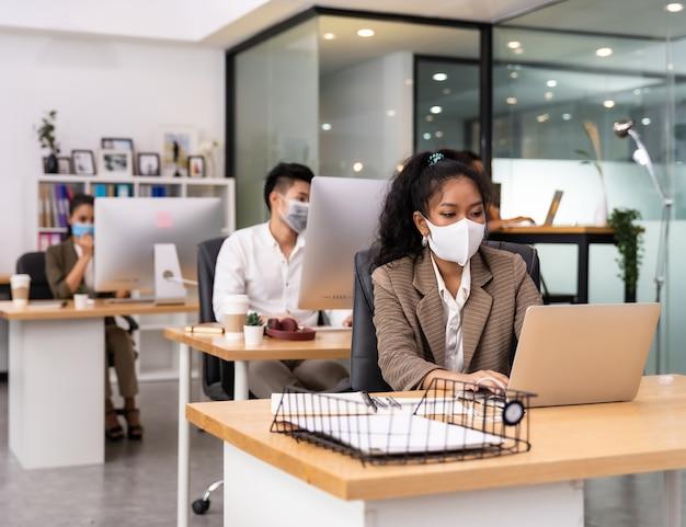 Gemischte rasse von afrikanischen und asiatischen geschäftsleuten, die gesichtsmasken im büro tragen