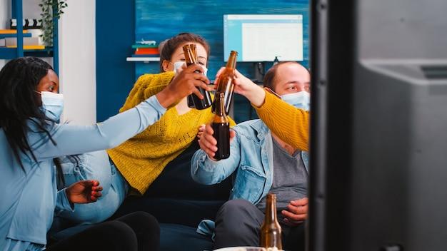 Gemischte rassen, die fernsehen und bierflaschen klirren, genießen die zeit und respektieren die soziale distanzierung mit schutzmasken gegen das covid-19-virus