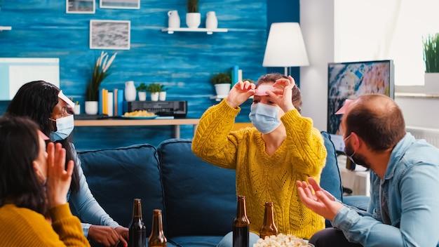 Gemischte rassen-freunde, die spaß beim spielen mit haftnotizen auf der stirn haben, bier trinken und eine neue normale party genießen