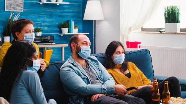 Gemischte rassen von freunden, die fernsehen, mann, der wegen des ausbruchs der coronavirus-pandemie eine fernbedienung mit gesichtsmaske hält, bier trinkt, sich entspannt, auf dem sofa im wohnzimmer sitzt