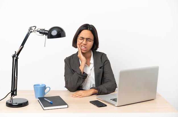 Gemischte rassenfrau des jungen geschäfts, die im büro mit zahnschmerzen arbeitet