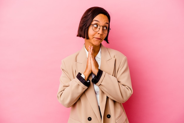 Gemischte rassenfrau des jungen geschäfts lokalisiert auf rosa wand, die betend zeigt, hingabe, religiöse person, die nach göttlicher inspiration sucht.